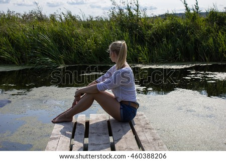 A young woman sits on a wooden bridge on the river