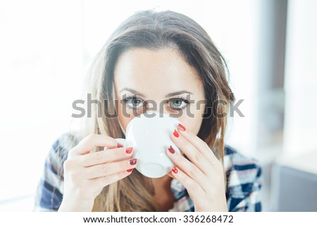 A young woman sitting at a table in a bar indoors drinking from a ceramic mug. Face Close-Up - stock photo