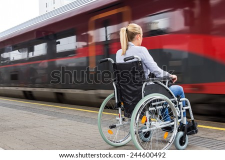 a young woman sitting in a wheelchair at a train station - stock photo
