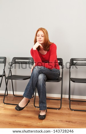 A young woman sitting in an empty waiting room and looking bored. - stock photo