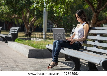 A young woman sitting on a bench, near the university, working o - stock photo
