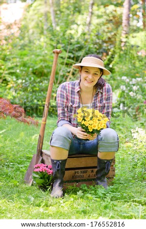 A young woman sitting on a crate holding a bouquet of flowers.