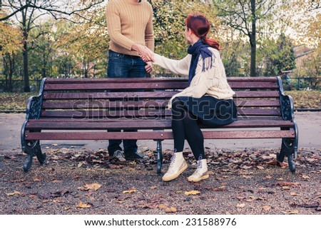 A young woman sitting on a park bench is meeting a man in the park and they are shaking hands