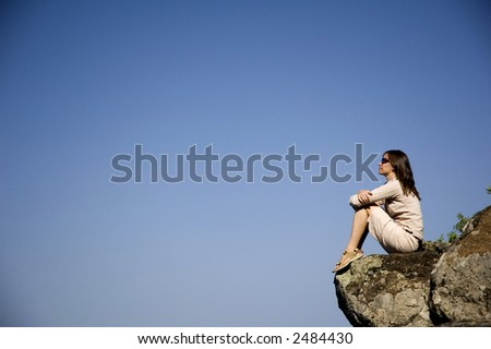 A young woman sitting on a rocky outcrop in the Caldera de Los Marteles in Gran Canaria - stock photo