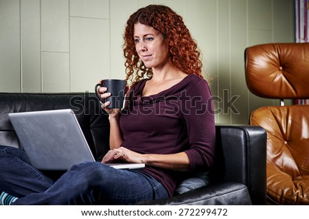 a young woman sitting on a sofa with a hot drink and using a laptop - stock photo