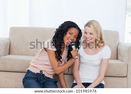 A young woman sitting on the floor with her friend is singing into a microphone - stock photo