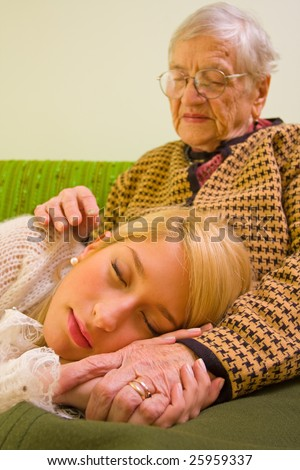 A young woman sleeping on her grandmother's feet - part of a series. - stock photo