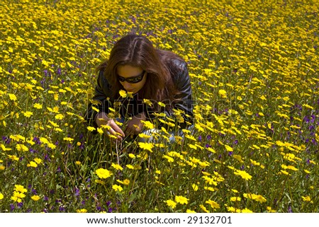 A young woman smelling yellow flowers