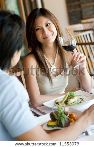 A young woman smiling whilst eating dinner at a restaurant - stock photo