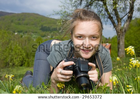 A young woman smiling whit a compact digital camera in her hand. - stock photo