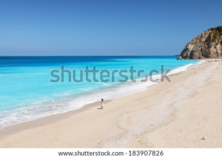 A young woman standig on the beach, looking at the sea - stock photo