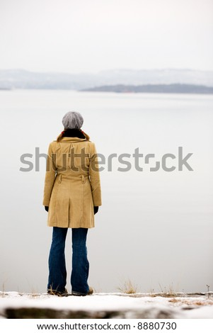 A young woman standing by the ocean in winter