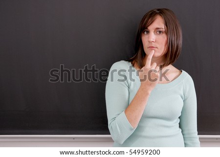 A young woman standing in front of a black board - stock photo