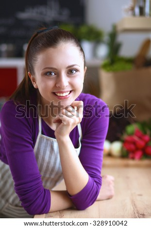 A young woman standing in her kitchen . - stock photo