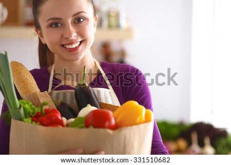 A young woman standing in her kitchen holding a bag of groceries. - stock photo