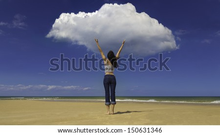 A young woman stands on a sandy beach, as if commanding the clouds, rainmaking/ Young woman on beach facing cloud - stock photo