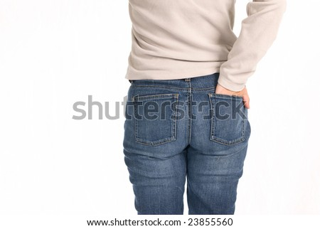 A young woman stands with her hand in her back pocket isolated on a white background. - stock photo