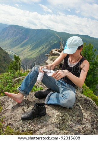 A young woman takes off on a halt hiking boots in the tracking