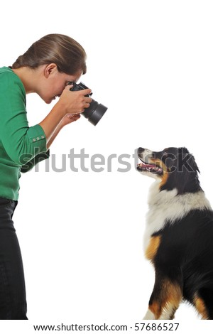 A young woman taking photographs of a willing dog, isolated on white. Space for text.