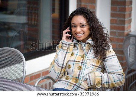 A young woman talking on her cell phone outdoors while seated at a cafe table. - stock photo