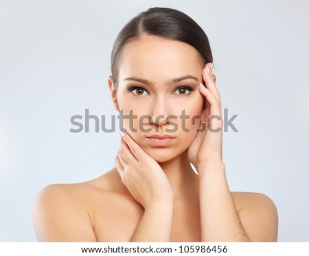 A young woman touching her face, isolated on white background - stock photo