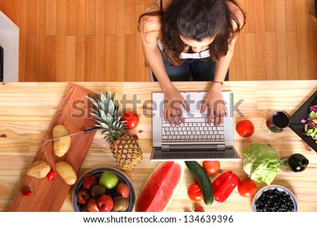 A young woman using a Laptop while cooking. - stock photo