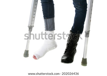 A young woman using crutches to help heal her recent foot injury.  isolated on white with room for your text. - stock photo