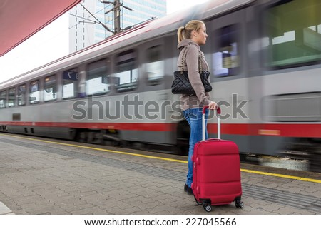a young woman waiting for a train at a railway station. train ride on holiday