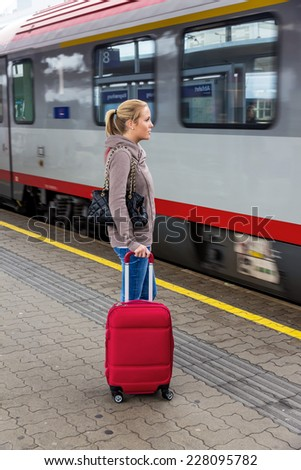 a young woman waiting for a train at a railway station. train ride on holiday - stock photo