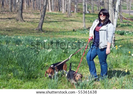 A young woman walking her two dogs in the park on a sunny day. - stock photo