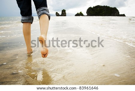 A young woman walks alone on a beach, just her feet and legs showing - stock photo