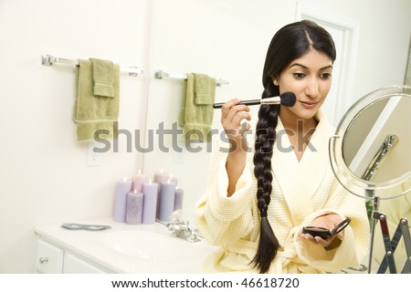 A young woman wearing a bathrobe is sitting on the sink in front of a mirror and applying makeup. Her long dark hair is braided and hanging over her shoulder. Horizontal shot. - stock photo