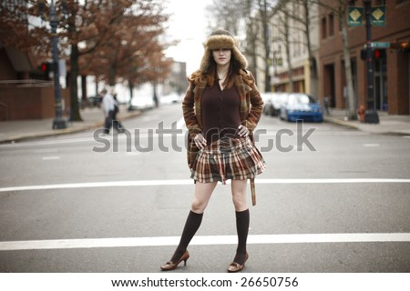 A young woman wearing a brown plaid skirt and coat.
