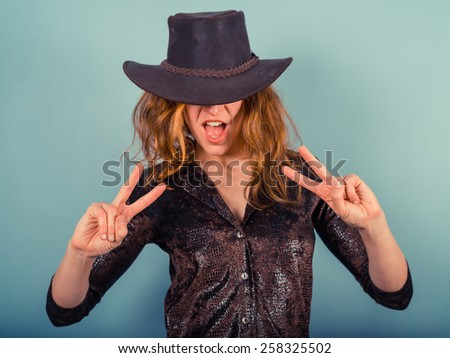 A young woman wearing a cowboy hat is showing the peace sign with her hands - stock photo