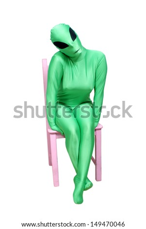 A young woman wearing a green alien body suit, sitting in a pink wooden chair.  Isolated on a white background with generous copyspace. - stock photo