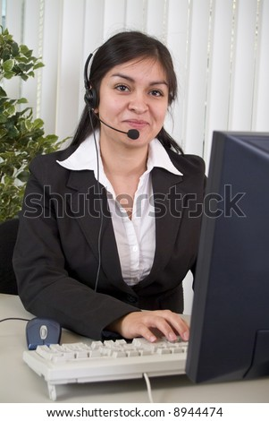 A young woman wearing a headset sitting in front of a computer monitor. - stock photo