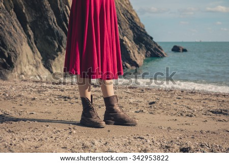 A young woman wearing a red dress and hiking boots is standing on the beach - stock photo