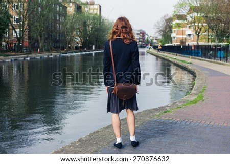 A young woman wearing a skirt and a jacket is standing by a canal in the spring - stock photo