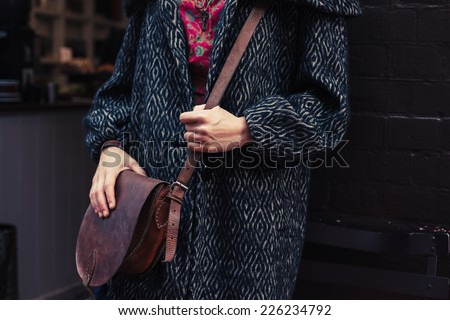 A young woman wearing a winter coat is standing in the street with a shoulder bag - stock photo