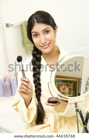 A young woman wears a bathrobe while holding a makeup brush and smiling at the camera. Her long dark hair is braided and hanging over her shoulder. Vertical shot. - stock photo