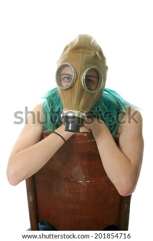 A young woman wears a Gas Mask while sitting backwards on an antique wooden chair. isolated on white with room for your text. - stock photo