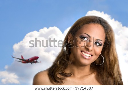 A young woman with a big smile on her face thinking about traveling or taking a vacation to an exotic place. - stock photo
