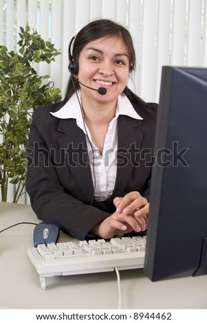 A young woman with a charming smile, working the helpdesk. - stock photo