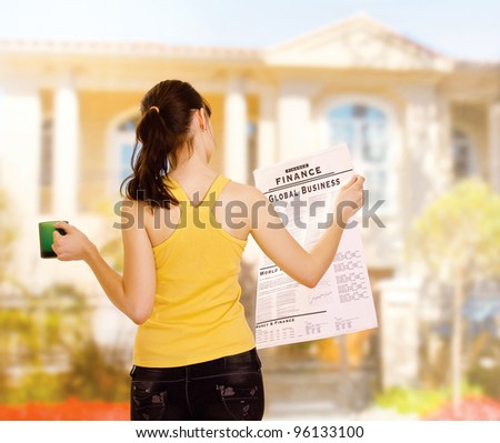 A young woman with a newspaper and a cup of tea outside, back-view - stock photo