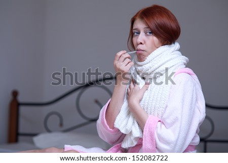 A young woman with a thermometer - stock photo