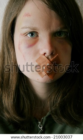 A young woman with a wound on her cheek and a plaster on her mouth. A victim of domestic violence keeping silent? - stock photo
