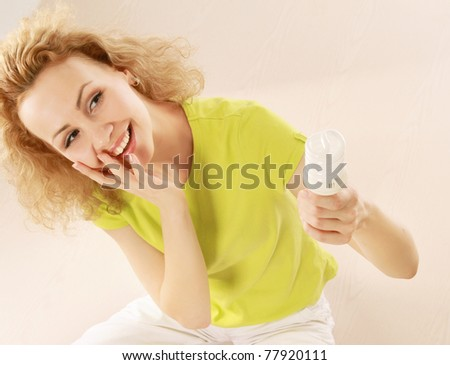 A young woman with an energy-saving bulb in her hands, sitting on the floor - stock photo