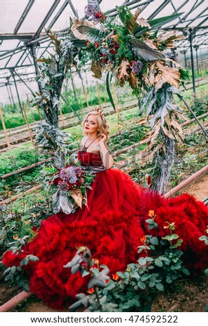 A young woman with flowers in greenhouses. Model in red cloud dress embracing near round flowers arch.