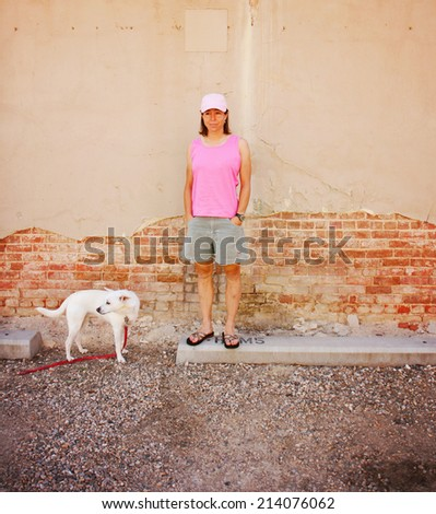 a young woman with her small dog toned with a warm filter - stock photo