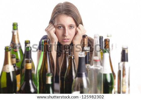 A young woman with long hair brunette sits amidst empty bottles on a table and looks desperate, isolated against white background. - stock photo